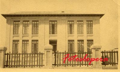 Vista frontal del Colegio Francisco Giner de los Ríos (hoy Miguel de Cervantes) ante de ser inaugurado. Detalle de los cristales pintados y las vallas de madera del recreo.